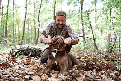 Man playing with dog in forest - p300m1499254 by Michelle Fraikin