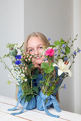 Portrait of smiling blond girl with bunches of flowers in sleeves of her dress - p300m2062439 by Petra Stockhausen