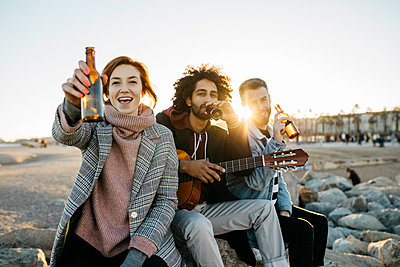Three happy friends with guitar toasting beer bottles at sunset - p300m2083400 by Josep Rovirosa