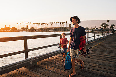 Father and son on pier with fishing rods, Goleta, California, United States, North America - p429m1504787 by JFCreatives