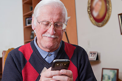 Senior man using mobile phone at home - p924m1174911 by REB Images