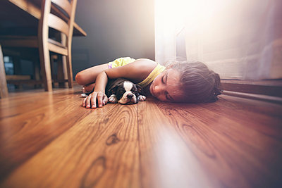 Girl lying on floor with sleeping Boston Terrier puppy - p924m1422824 by Rebecca Nelson