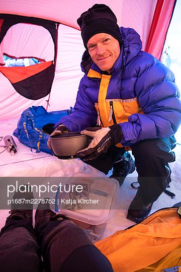 Man preparing food inside of tent in winter - p1687m2278782 by Katja Kircher