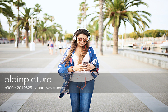 Portrait of woman wearing sunglasses listening music with headphones while looking at smartphone - p300m2012625 von Juan Novakosky