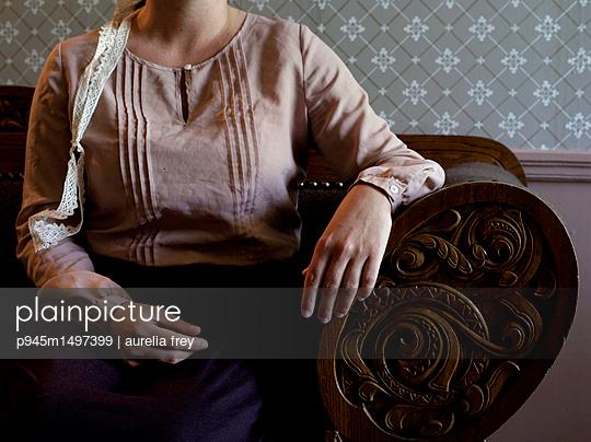 Woman sitting on sofa - p945m1497399 by aurelia frey