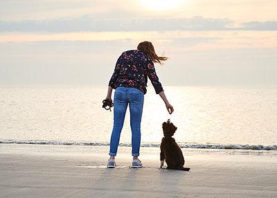 Frau mit Hundewelpen am Strand - p1124m1223978 von Willing-Holtz