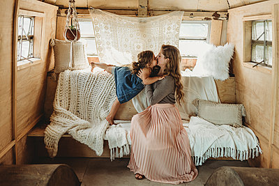 Mother and daughter kissing in boho studio setup - p1166m2130807 by Cavan Images