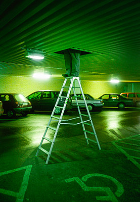Janitor standing on ladder in garage - p1418m1571520 by Jan Håkan Dahlström