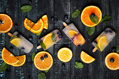Homemade detox popsicles with blueberries, orange slices and mint leaves on black wood - p300m1581608 von Retales Botijero