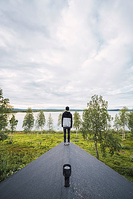 Finland, Lapland, man standing on roof of a house at a lake - p300m2060803 by Kike Arnaiz
