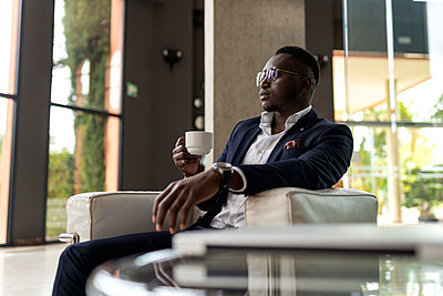 Young male businessperson contemplating while having coffee hotel - p300m2251090 by Ezequiel Giménez