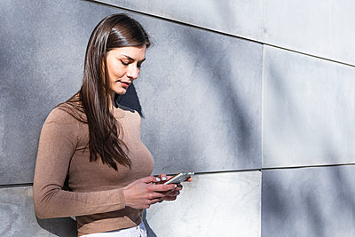 Smiling female entrepreneur using smart phone while leaning on wall - p300m2256487 by NOVELLIMAGE