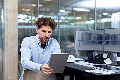 Young businessman using digital tablet while sitting at desk in office - p300m2265172 by Florian Küttler