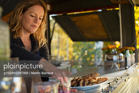 Female food cart owner arranging pastries - p1023m2287069 by Martin Barraud