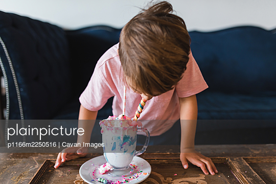 Boy drinking a colorful milk shake in front of a vintage blue couch. - p1166m2250516 by Cavan Images