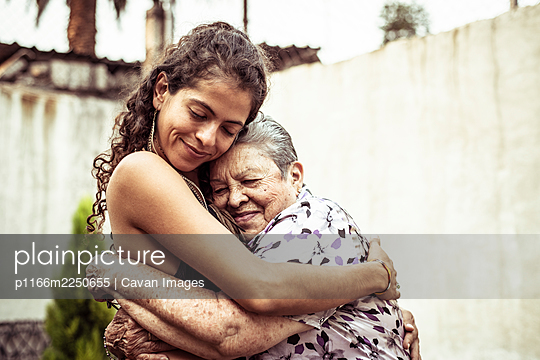 Mexican women smile in loving hug embrace on summer street Mecxico - p1166m2250655 by Cavan Images