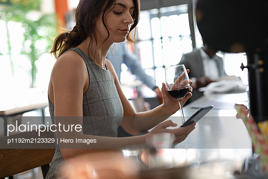 Businesswoman texting on phone with red wine - p1192m2123329 by Hero Images