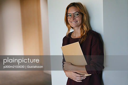 Smiling businesswoman leaning against a wall holding folder - p300m2103030 by Gustafsson
