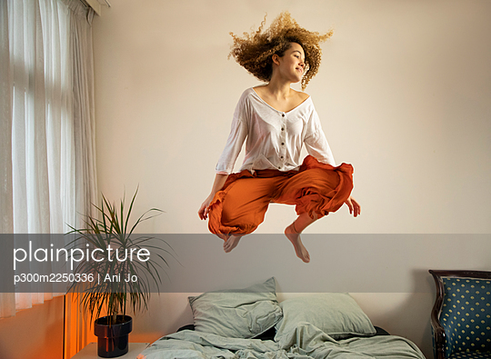 Happy young woman jumping over bed at home - p300m2250336 by Ani Jo