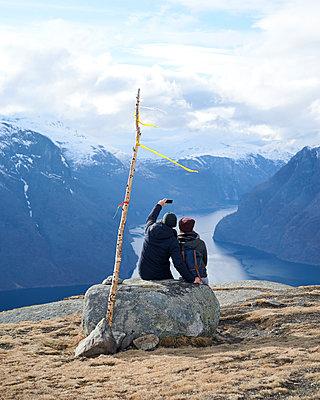 Paar sitzt auf Stein am Aurlandsfjord - p1124m1133165 von Willing-Holtz