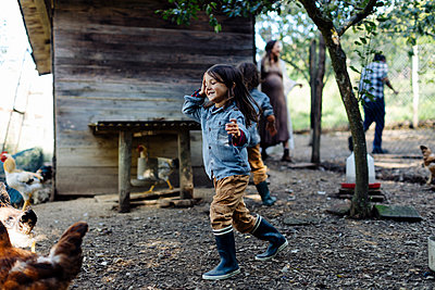 Family in a chicken pen on an organic farm - p300m2144735 von Sofie Delauw