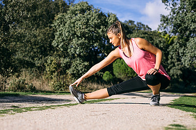Mid adult woman stretching on footpath in forest during sunny day - p300m2273490 by Andrés Benitez