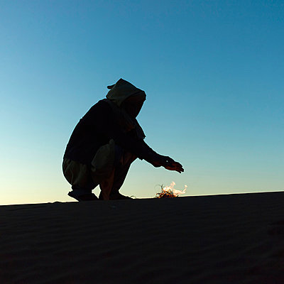 Silhouette of a man heating his hands over a small fire in the desert; Souss-Massa-Drass, Morocco - p442m824161 by Keith Levit