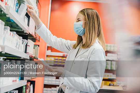 Pharmacist wearing protective face mask while working in chemist store - p300m2243130 by Mareen Fischinger