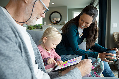 Grandparents watching granddaughter coloring on digital tablet - p1192m2046576 by Hero Images