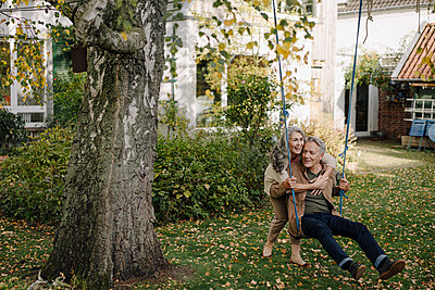 Happy woman embracing senior man on a swing in garden - p300m2155043 by Gustafsson