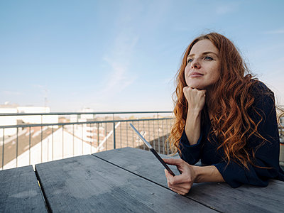 Redheaded woman with tablet on rooftop terrace - p300m2167255 by Kniel Synnatzschke