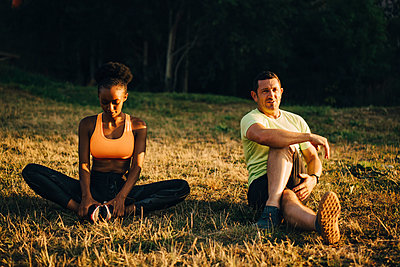 Sportsman and sportswoman doing relaxation exercise while sitting on grassy area - p426m2270784 by Maskot