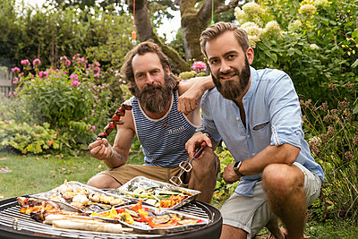 Two men at the barbeque in the garden - p788m2027425 by Lisa Krechting