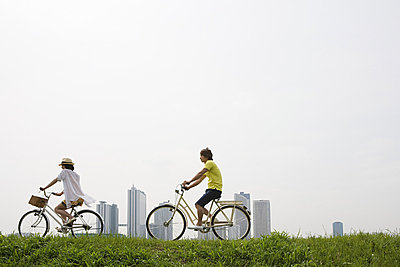 Young couple cycling - p9246747f by Image Source