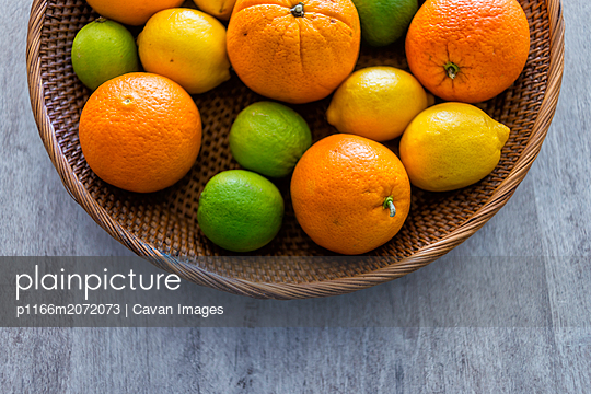 Above view of a fruit basket on a table with mandarins and a melon - p1166m2072073 by Cavan Images