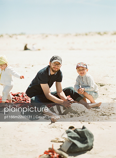 A happy family building sand castles at the beach - p1166m2200131 by Cavan Images