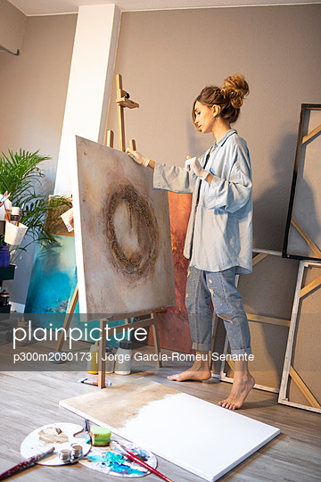 Young woman looking at finished painting in her atelier - p300m2080173 by Jorge Garcia-Romeu Senante