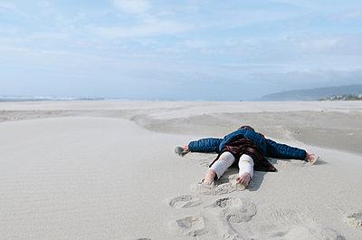 Girl lying on sand at beach against sky - p1166m1485523 by Cavan Images