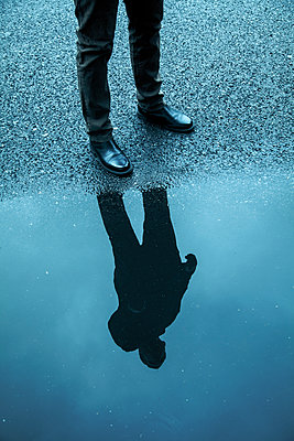 Man standing at puddle  - p1248m2193193 by miguel sobreira
