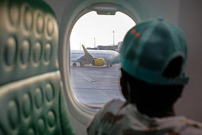 Boy looking out airplane window - p1307m2295548 by Agnès Deschamps