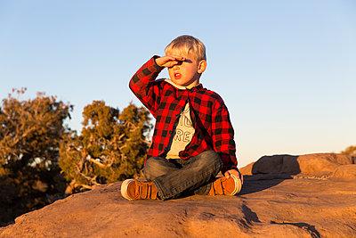 Boy sitting on rock - p756m1584493 by Bénédicte Lassalle
