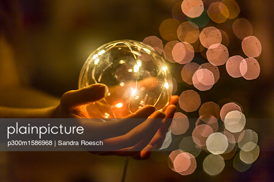 Hands of girl holding shining crystal ball - p300m1586968 von Sandra Roesch