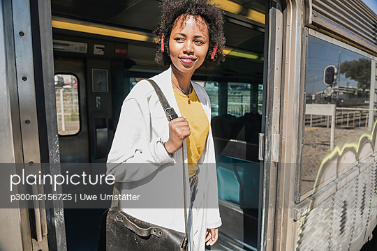 Smiling young woman standing in train door - p300m2156725 by Uwe Umstätter