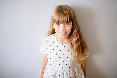 Blonde girl in a polka dot dress standing by a wall smiling - p1414m2044847 by Dasha Pears