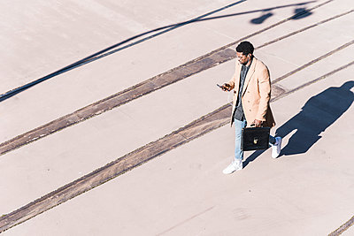 Businessman walking outdoors with briefcase, cell phone and earphones - p300m1568541 by Uwe Umstätter