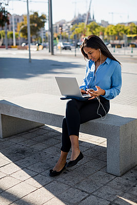 Businesswoman using laptop, holding smartphone - p300m2070105 by Mauro Grigollo