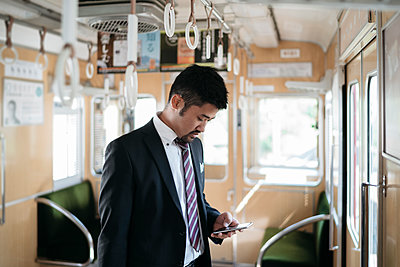 Young businessman using cell phone on a train - p300m2140622 by Juri Pozzi