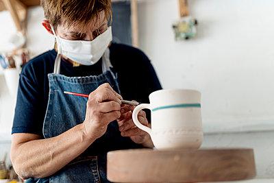 Female artist painting cup in ceramic workshop - p300m2240713 by Ezequiel Giménez