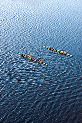 Elevated view of two rowing eights in water - p300m975556f by zerocreatives
