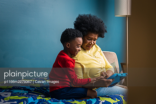 Smiling boy and grandmother using digital tablet while sitting in bedroom at home - p1166m2279367 by Cavan Images
